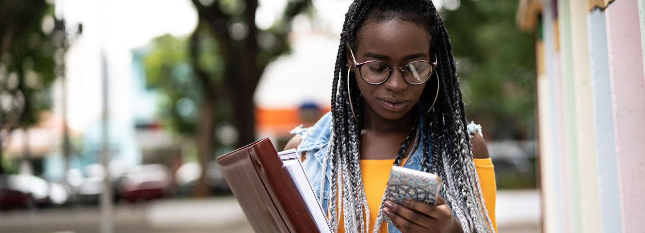 woman wearing glasses walking outside carrying books and using phone