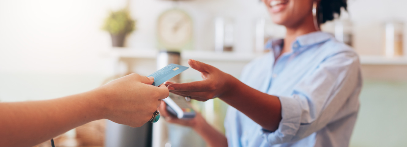 Close up of someone's hand holding out a credit card for a woman with a card reader.
