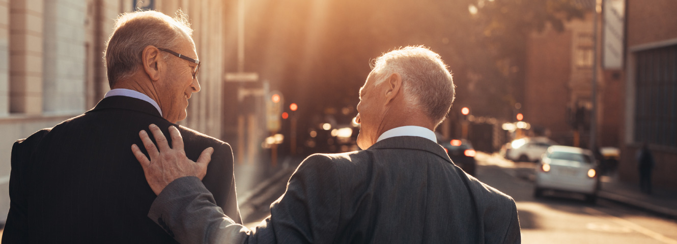 Two older businessmen in suits smiling at each other and walking down a city street.