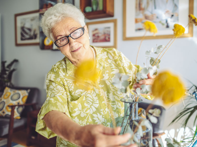 Elderly woman tending to yellow flowers.